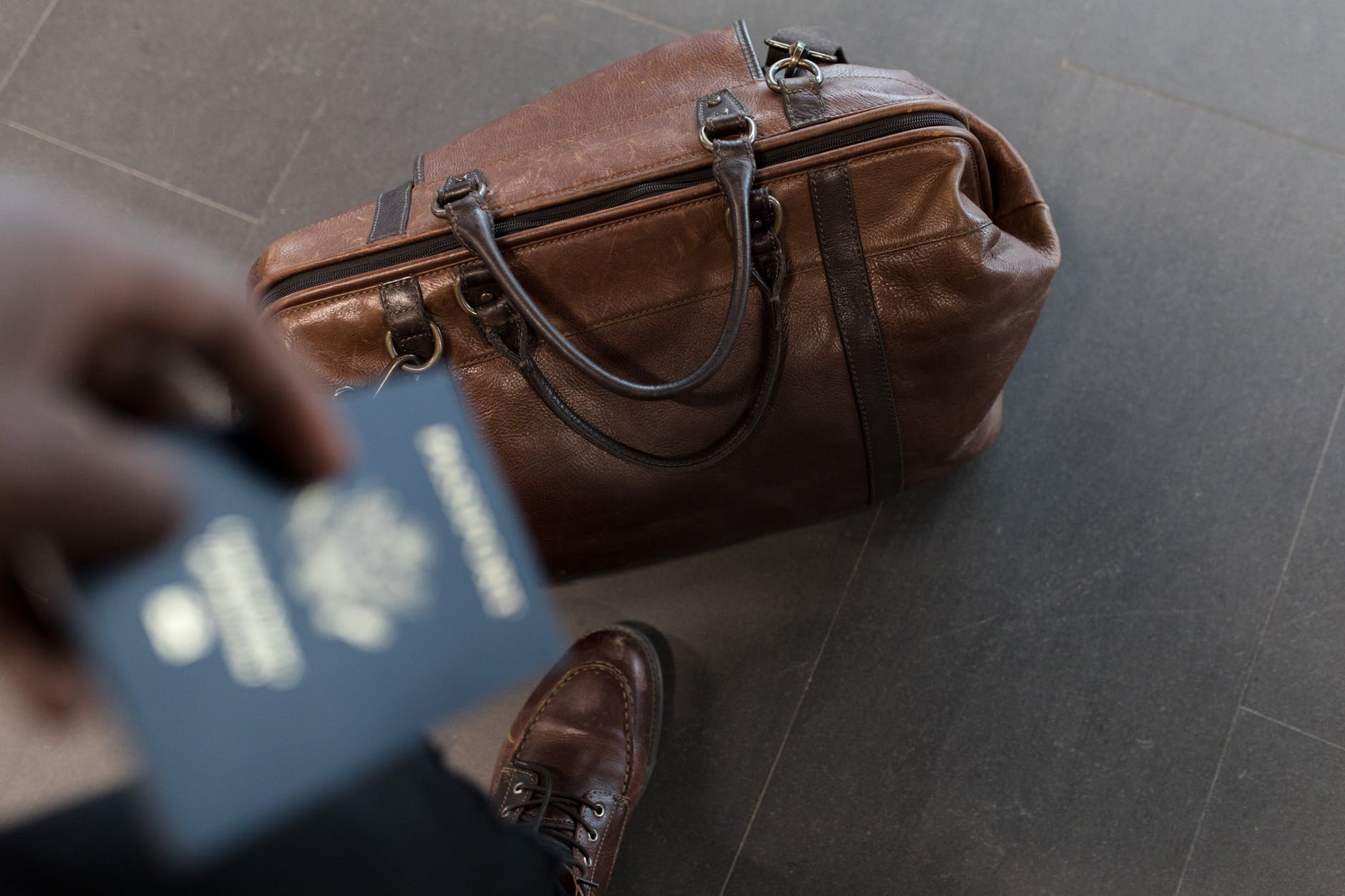a man holding a passport while his bag is on the ground