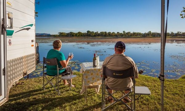 an elderly couple enjoying wine in front of a lake